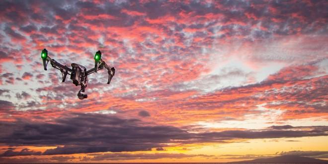 un drone volant au dessus de l'eau pendant un coucher de soleil