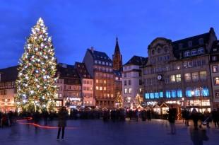 un sapin de noel illuminé sur la place principale d'une ville
